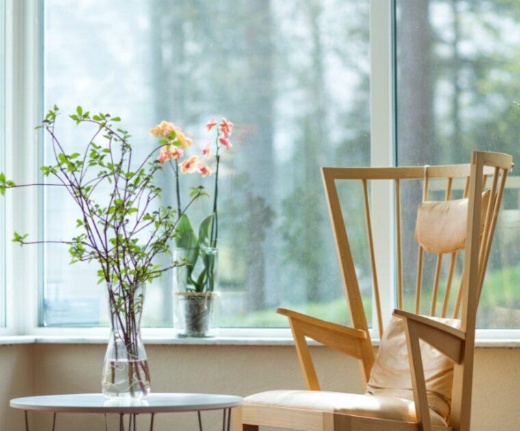 Träfåtölj framför ett fönster med blommor i